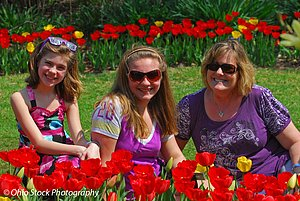 Three smiling girls sitting among red flowers at the Cincinnati Zoo during the Zoo Blooms event photo by Ohio Stock Photography D1F530
