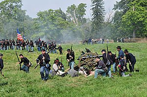 Civil War Reenactors staging a mock battle at Hale Farm and Village in Bath Township, Summit County, Ohio - Union soldiers running with guns, firing cannons, and carrying the American flag. Horizontal photo by Ohio Stock Photography D41T300