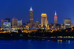Cleveland Ohio Skyline at night with building lights on,  blue sky and Lake Erie. Horizontal photo by Ohio Stock Photography FX24U-785