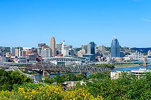 Cincinnati Ohio Skyline with the Ohio River and yellow flowers in the foreground. Horizontal photo by Ohio Stock Photography FX9U-2127