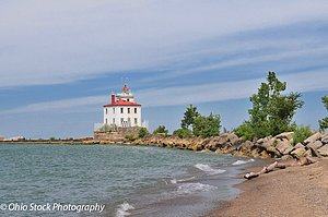 White lighthouse with red roof and waves breaking on shore - Fairport Harbor West Breakwater Lighthouse at Headlands Beach State Park photo by Ohio Stock Photography D6B68